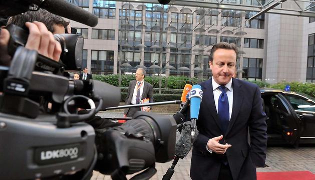 El primer ministro británico, David Cameron, habla con los periodistas a su llegada a la cumbre de dos día de los Veintisiete.