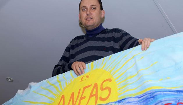 Ignacio Solla posa junto a un cartel de Anfas, en el local que esta asociación tiene en Pamplona.