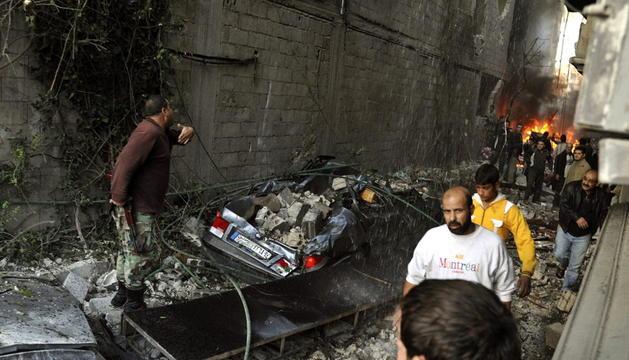 Un grupo de sirios observan el escenario de un ataque con coche bomba