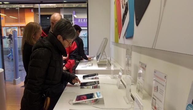 Algunas personas miran unos tablets en uno de los pequeños comercios que han abierto en festivos.