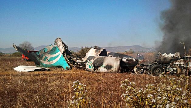 Un bombero extingue las llamas tras estrellarse un avión cerca del aeropuerto de Heho en Birmania
