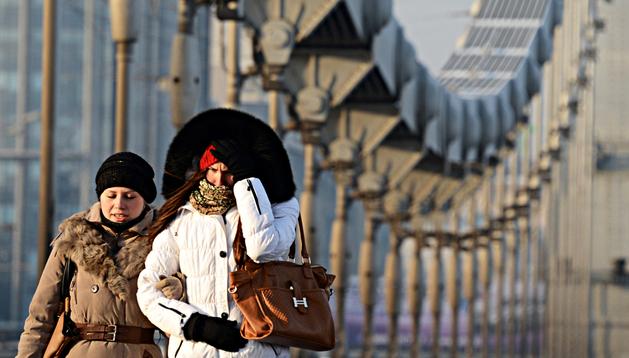 Dos jóvenes pasean abrigadas por el puente Krymsky de Moscú