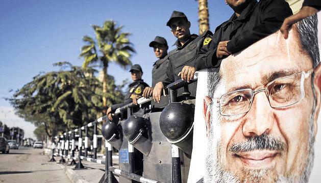 Policías fuera del Constitucional egipcio tras un retrato de Mursi.