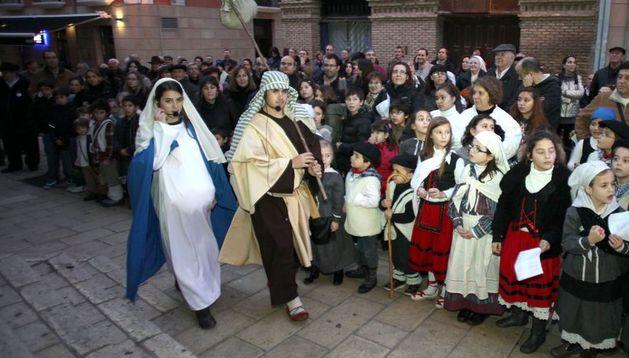 María y José pasan por la plaza Vieja de Tudela rodeados de niños participantes en el belén viviente y el público asistente.