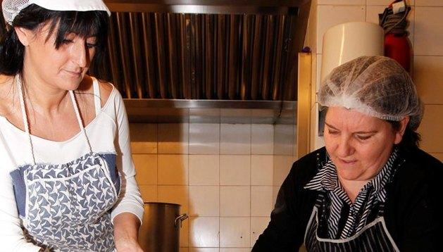 Soraya Avelino (voluntaria) y Lilyana Balabanova vuelcan la sopa caliente en el termo industrial