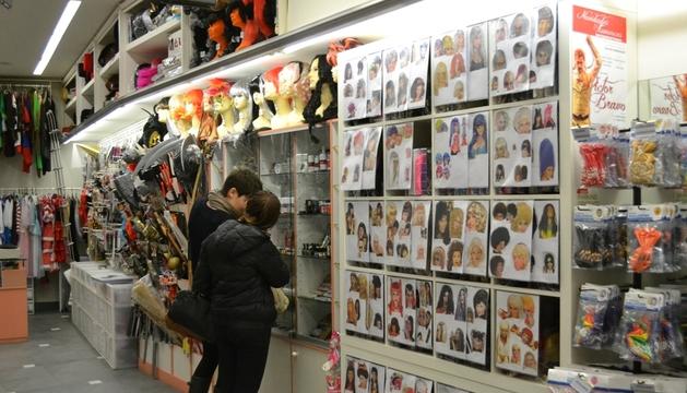 Dos jóvenes ojean complementos para su disfraz este viernes en Pamplona