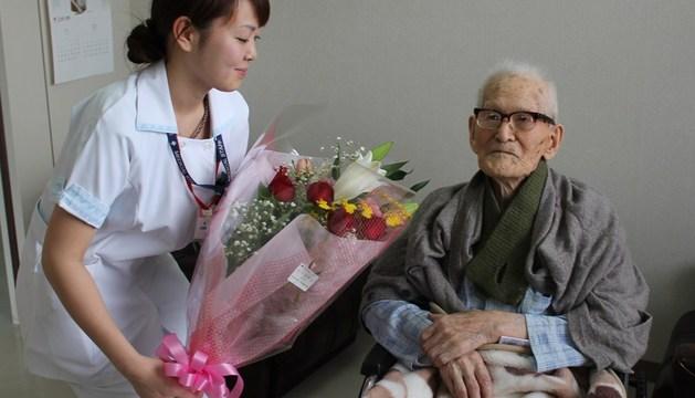 Jiroemon Kimura recibe un ramo de flores al convertirse en el hombre más anciano del mundo