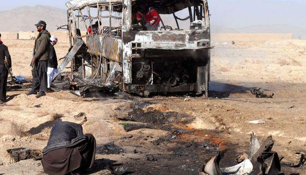 Oficiales de seguridad paquistaníes inspeccionan los restos de uno de los autobuses atacados
