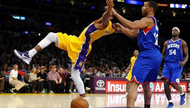El jugador de los Sixers de Filadelfia Evan Turner (dcha.) hace falta al base de los Lakers de Los Ángeles Darius Morris (izda.), durante un encuentro de la NBA celebrado en Los Ángeles, en California