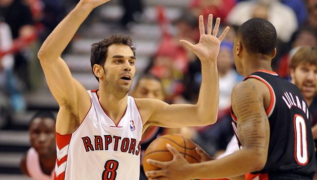 El jugador de los Raptors José Calderón marca a Damian Lillard, de Trail Blazers.