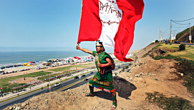 Un poblador de la limeña zona de Huaycán ondea una bandera de Perú