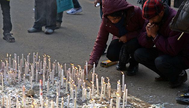 Un joven enciende una vela en recuerdo de la estudiante fallecida