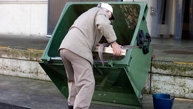 Un anciano extrae de un contenedor de basura una caja de congrio y unas lechugas en Pamplona