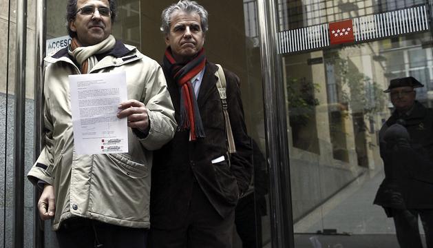 Los portavoces de la Plataforma de equipos directivos de centros de salud de Madrid, Paulino Cubero (i) y Alejandro Tejedor (2i), muestran el documento de dimisión de 322 cargos de 137 ambulatorios.