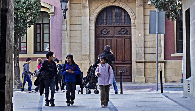 Unos niños caminan ante la fachada de la casa consistorial de Estella