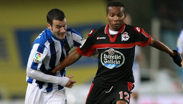 El delantero de la Real Sociedad Imanol Agirretxe (izq), intenta alcanzar un balón controlado por el brasileño del Deportivo de La Coruña Paulo Assunção durante el partido que disputaron este fin de semana
