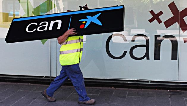 Un operario lleva sobre sus hombros uno de los carteles de CAN, tras la llegada de Caixabank