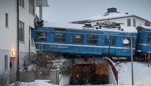 La policía inspecciona el lugar donde un tren ha colisionado con una vivienda tras descarrilar en Saltsjoebaden.