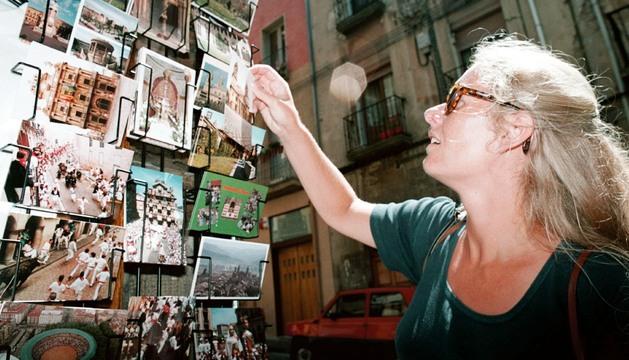 Una turista compra postales en un comercio pamplonés