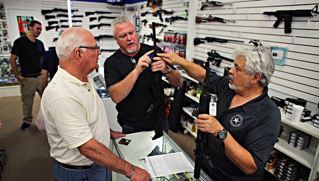 Dos vendedores de una tienda de armas de Pompano Beach (Florifa) explican el funcionamiento de una de ellas a un cliente