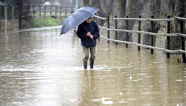 Un vecino atraviesa el paseo de la Magdalena inundado por el desbordamiento del Arga