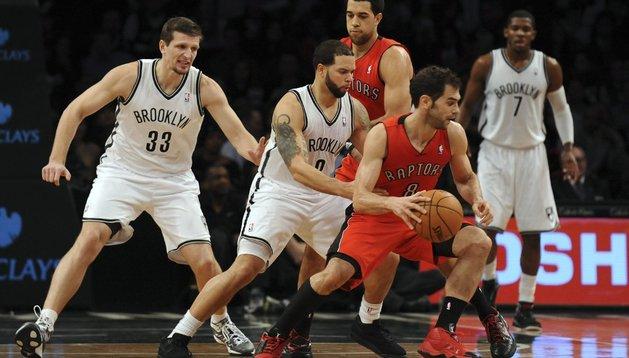 El jugador de Raptors José Calderon (d) conduce el balón ante los defensores de los Nets de Brooklyn