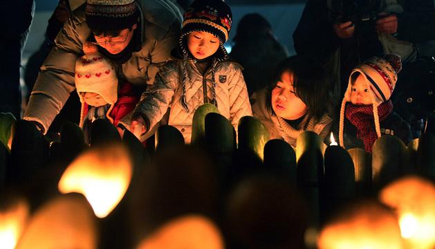 Una familia durante la oración en Kobe