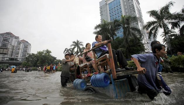 Residentes avanzan por una calle inundada en Yakarta