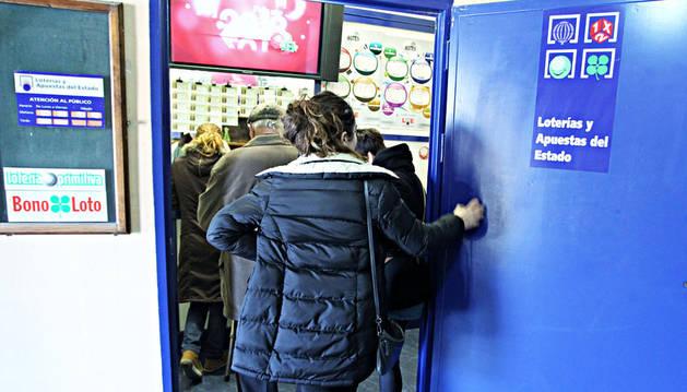 Varias personas esperan a comprar un décimo o realizar una apuesta en una administración de loterías de la capital navarra