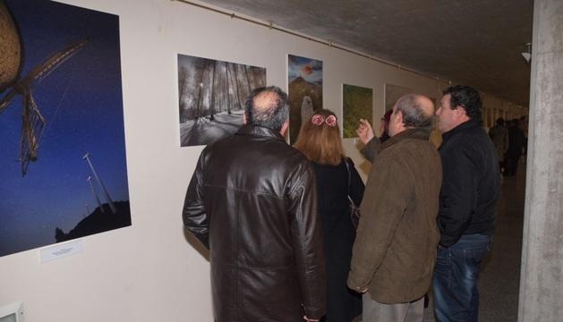 Varias personas contemplan una de las imágenes que incluye la exposición