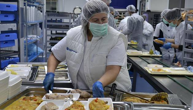 Una trabajadora, emplatando la comida