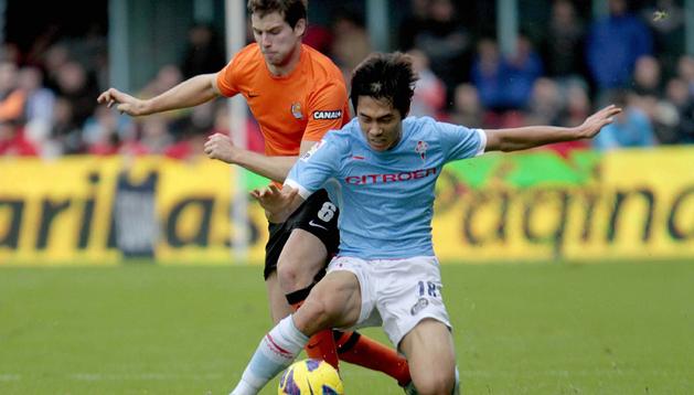 El delantero coreano del Celta de Vigo Ju Young Park (d) intenta controlar el balón presionado de cerca por el defensa de la Real Sociedad Iñigo Martínez