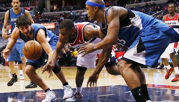 Rubio (izda.) y Cunningham (dcha.) de los Timberwolves, luchan por un balón con A.J. Price de los Wizards
