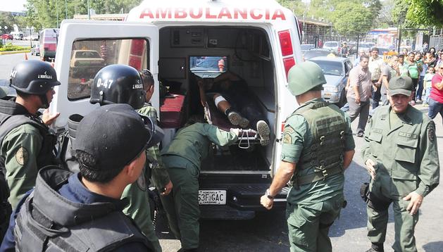 Miembros del Ejército ayudan a introducir en una ambulancia a uno de los heridos