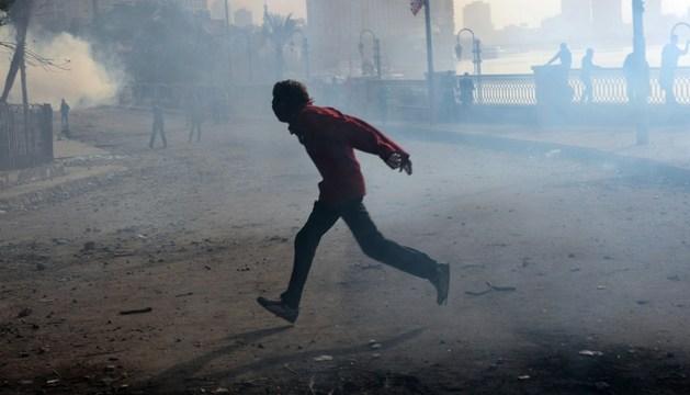 Un hombre corre por una calle cercana a la plaza Tahrir de El Cairo durante los disturbios