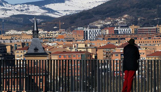 Una persona observa el barrio de la  Rochapea desde el mirador del paseo de Ronda.