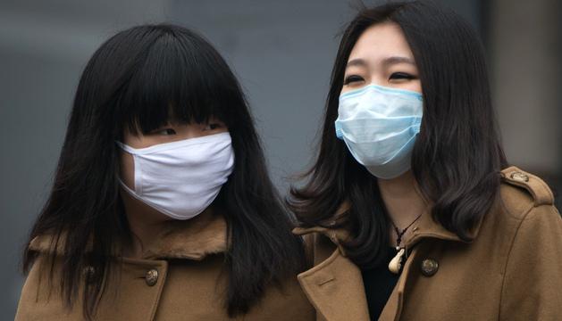 unas jóvenes chinas llevan mascarilla por la contaminación.