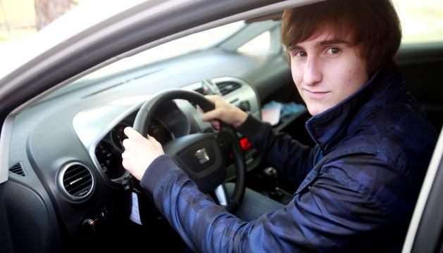 Un joven coge el volante en una clase de autoescuela.