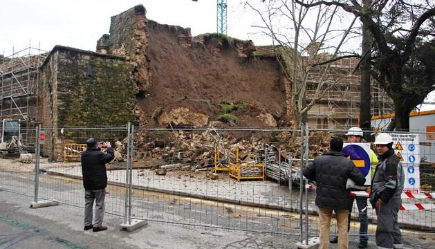 Varias personas observan el derrumbe de la muralla