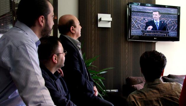 Unos hombres ven una intervención televisiva.