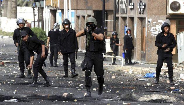 Un policía egipcio (c) se dispone a disparar un bote de gases lacrimógenos contra unos manifestantes