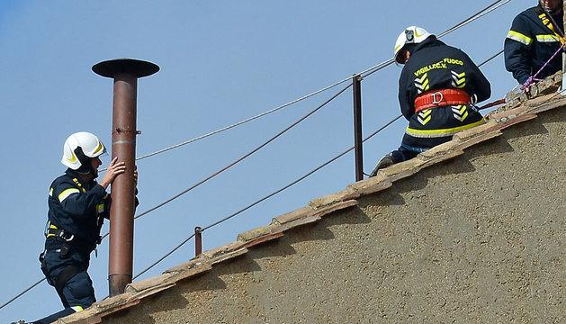 Operarios del Vaticano colocan la chimenea.