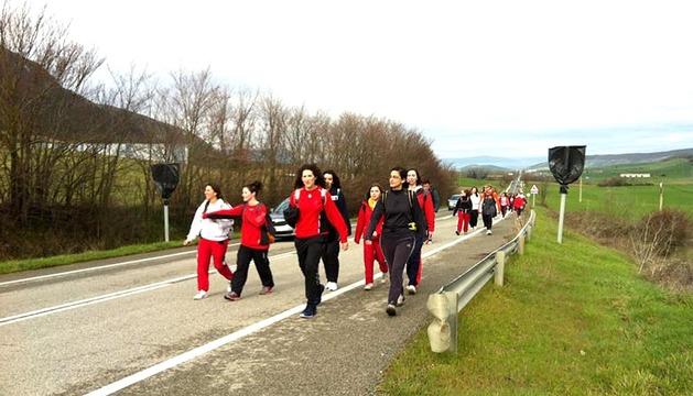 Varios peregrinos caminan por la carretera de entrada a Monreal