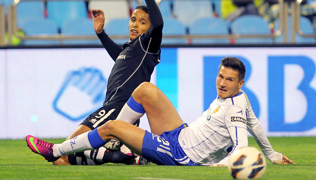 El centrocampista húngaro del Zaragoza Adam Pinter (d) y el delantero marroquí del Granada Youssef El Arabi luchan por el balón durante el partido correspondiente a la vigésimo séptima jornada de Liga que disputaron en el estadio de La Romareda