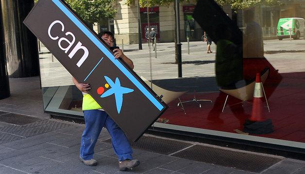 Imagen de archivo del momento de cambio de logotipo de la oficina de Caixabank.