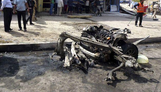 Iraquíes inspeccionan la zona en la que ha explosionado un coche bomba en Bagdad