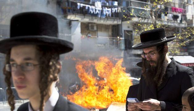 Varios judíos ultraortodoxos rezan mientras queman productos con levadura conocidos como