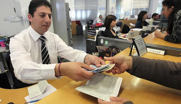 Un empleado de una sucursal del Banco Laiki entrega el dinero retirado por uno de sus clientes en Nicosia, Chipre.