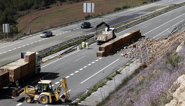 Operarios del servicio de conservación de carreteras del Gobierno de Navarra intentan habilitar un carril para el paso de los vehículos en la A-12