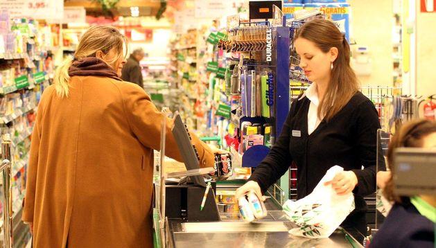 Una cajera atiende a una mujer en un supermercado